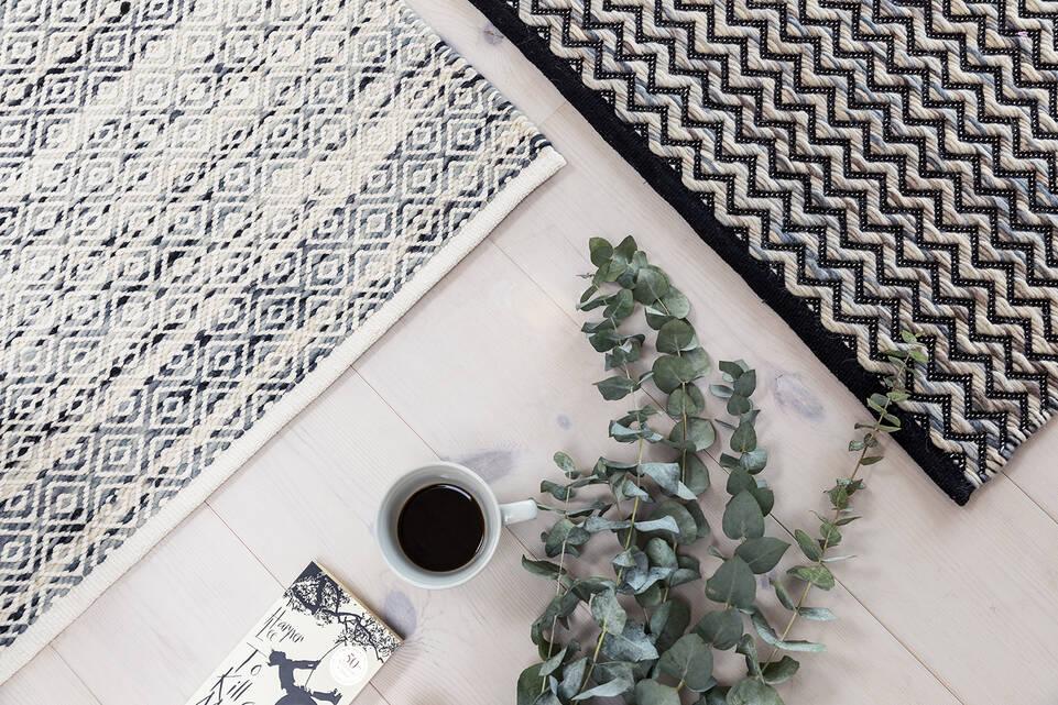 Svart / grått  röllakan / dorri med cotton mws - teppe i en stue.
