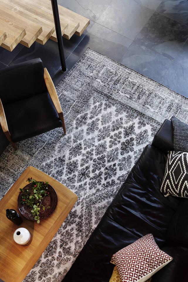 Alfombra colored vintage - persien / iran negra / gris  en salón.