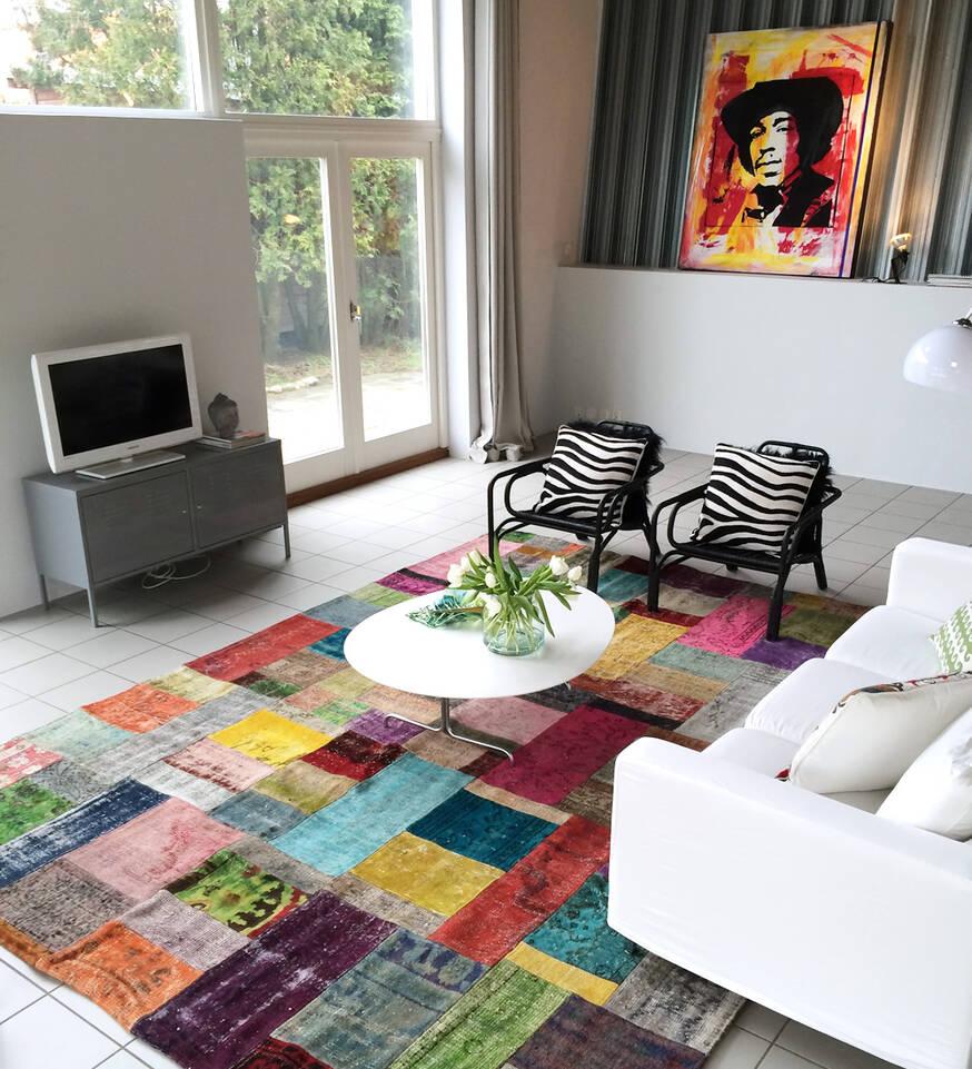 Alfombra patchwork multicolor cuadrada en salón.