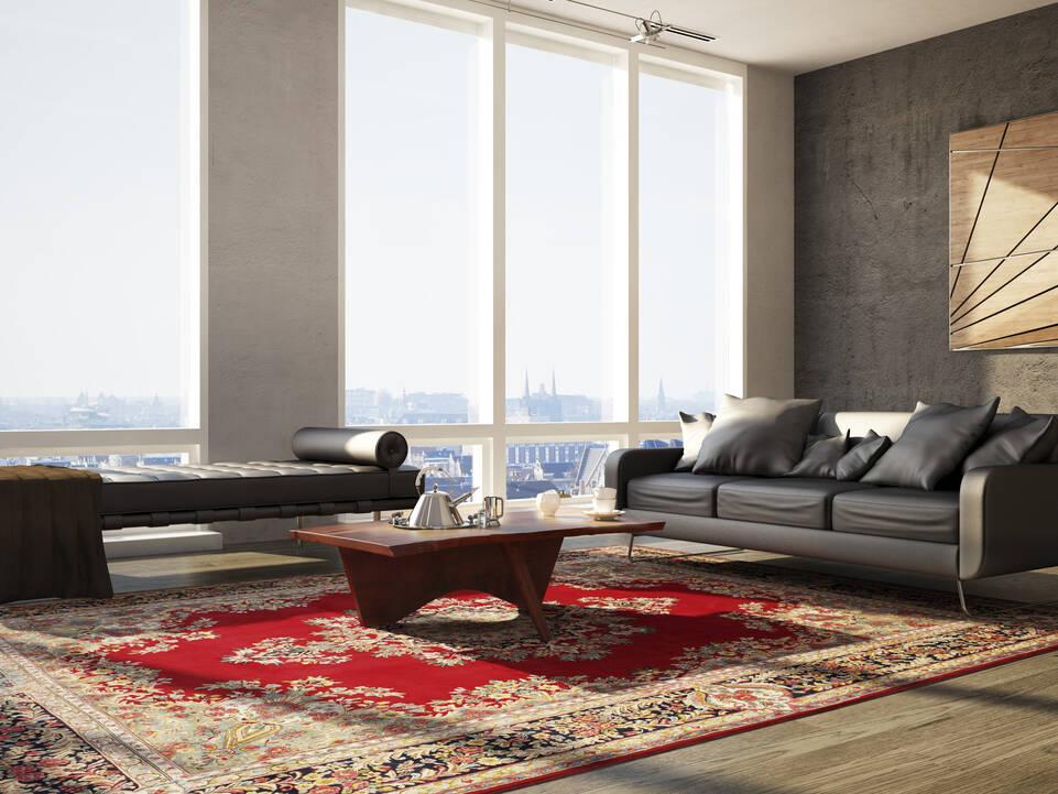 Rødt avlangt kerman - teppe i en stue.